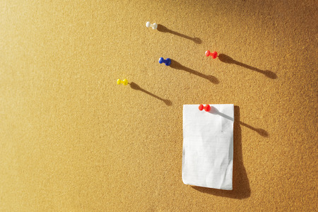 Orange Cork board with one bulletin paper note pinned and several different color pins above. Warm sunlight from the side