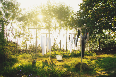 Freshly washed laundry drying on the string outside in the backyard of the farm on a warm bright sunny day