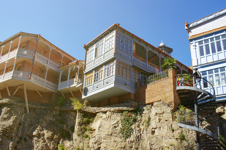 Traditional Georgian style architecture on the cliffs in Tbilisi old town. Wooden houses with colorful carved balconies 免版税图像