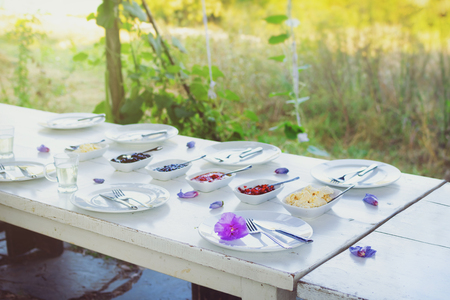 Outdoor white vintage table set for breakfast. Nicely decorated with fresh violet flowers and delicious food