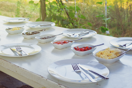 Outdoor white vintage table set for breakfast with empty plates ready for eating
