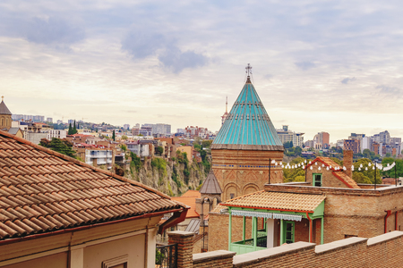 Sky over the Tbilisi Old Town neighborhood with a view on church tower and vivid red brick houses with their rooftops. Tbilisi, Georgia.