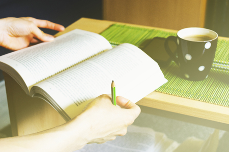 Young woman holding book and pencil for taking notes and enjoying with hot coffee and cell phone on the table 免版税图像