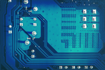 Blue side of motherboard circuit with soldered contacts and texture. High-tech abstract background with digital and new-age computer technology concept