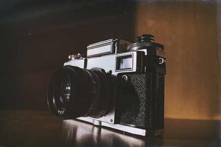 Old style retro analog film camera standing on the shelve with sun shining from the side