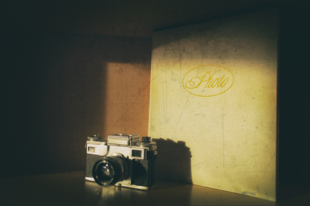 Old fashion retro analog camera standing beside big leather photo album slightly in the shadow. Old damaged photo with scratches 免版税图像