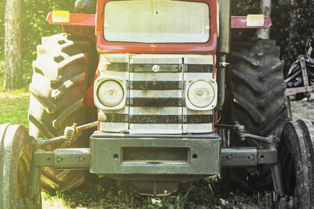 Old style retro tractor half color half black and white. Sun shining from the side
