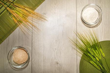 Kitchen bread making wooden background with bowls of wheat and fresh whole grains