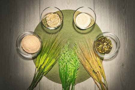Mix of different kinds of flour in the bowls with fresh wheat and barley grains.
