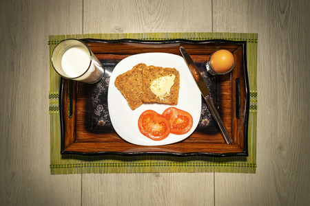 Simple breakfast with eggs, milk, tomato and butter on toasted bread nicely served on wooden vintage tray top view