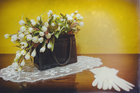Black leather vintage purse filled with flowers standing on glass surface with white lace gloves like decoration 免版税图像