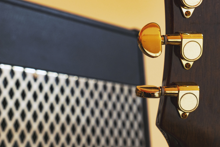 Guitar head with golden tuners in front of powerful vintage guitar amplifier with shiny metal grill