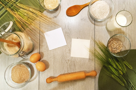 Fresh barley, wheat, bakery and bread ingredients on wooden background with empty notes, top view 免版税图像
