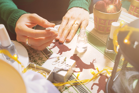 Young girl polishing nails while preparing herself for new years celebration. Decoration on the table 免版税图像