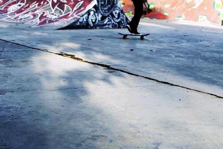 Young skateboarder skating inside of modern skatepark. Skateboard background 免版税图像
