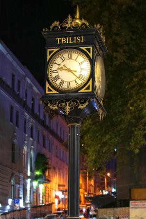 Vintage street clock on Shota Rustaveli avenue in Tbilisi, georgia. Night time 免版税图像