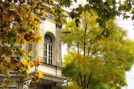 Beautiful old building with window on the corner of the street in Tbilisi old town, autumn foliage colors, Georgia