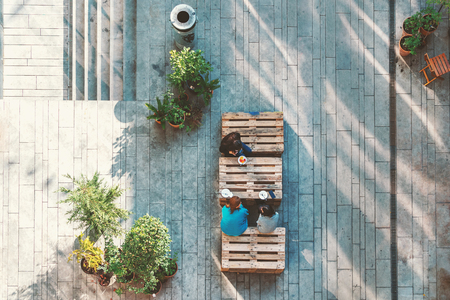 People hanging out in the garden, sitting on the pallets eating cakes. View from above. Concept 免版税图像