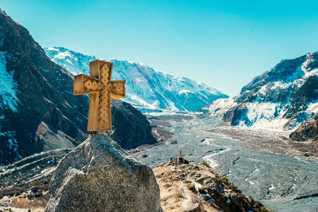 Amazing view alongside Georgian military road, high in the Caucasus mountains. Winter time, high mountain peaks covered with snow. Wooden cross beside the road.