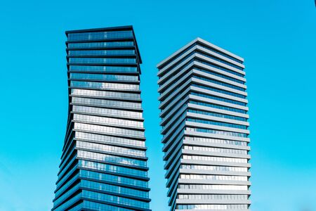 Two modern tall business skyscrapers with lot of glass windows against blue sky - Image