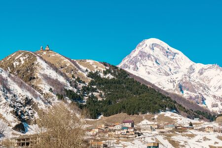 Gergeti Trinity Church (Tsminda Sameba), Holy Trinity Church above village Gergeti in Georgia, with high Mount Kazbegi behind - Image