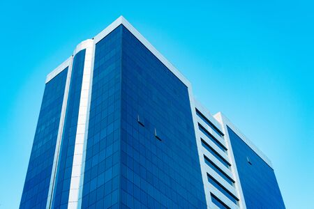 Modern tall business skyscraper with lot of glass windows against blue sky - Image