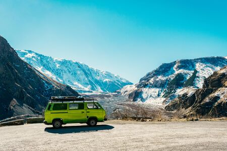 Vintage classic van parked beside the road among the high Caucasus peaks on the far north of Georgia. Breath taking view.