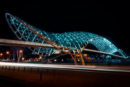 Georgia, Tbilisi - 05.02.2019. - Night view over illuminated famous Bridge of Peace in center of Tbilisi city. Car light trails - Night photography