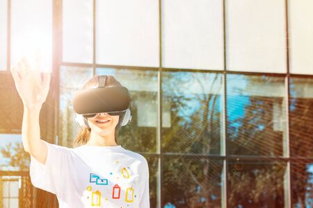 Beautiful young female in white t-shirt using virtual reality headset reaching with hand and smiling. VR designed background 免版税图像