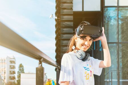 Beautiful young female in white t-shirt putting on virtual reality headset and looking into camera with a big cute smile. Modern glass business building facade in the background.