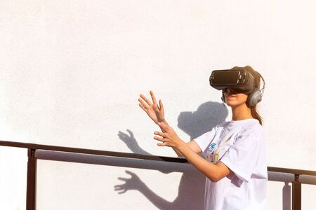 Beautiful young female in white t-shirt wearing virtual reality headset with hands reaching in front. White wall surface in the background. Фото со стока