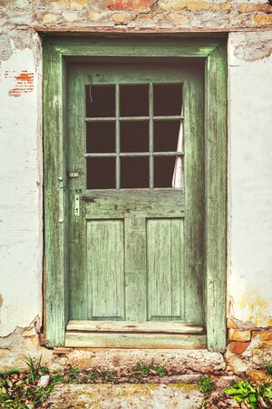 An old rotten wooden door on crumbling house. Vintage matte look effect.