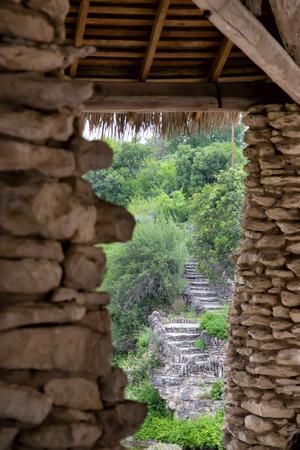 asian rock pillars and grass roof overlooking green rock garden