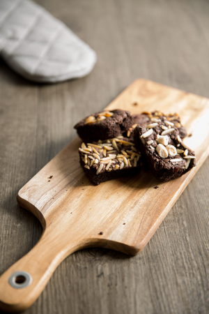 Assorted chocolate cake brownies with nuts topping on wooden board
