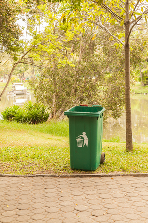 Green bin on the tropical garden in the park.