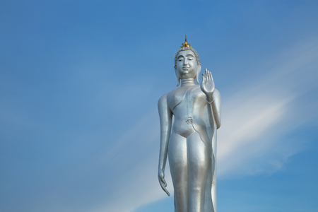 Walking Buddha image silver on a beautiful sky background.