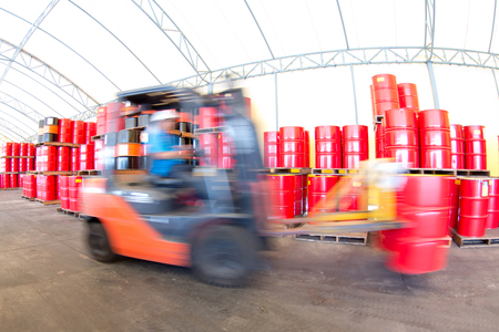 forklift handling the oil drum in ware house