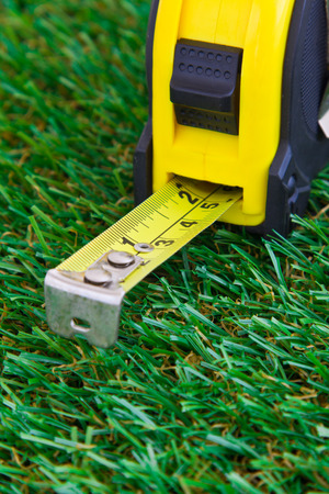 Close up of measuring tape with magnetic head on grass