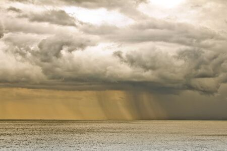 Storm clouds with rain over the sea