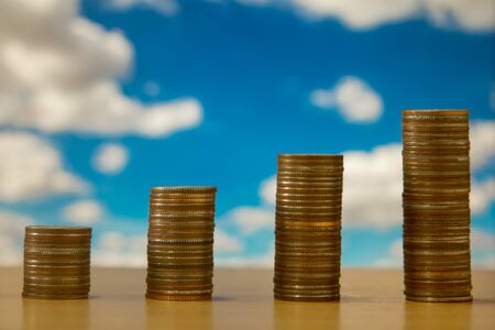 Coin stacks with blue sky background Stock Photo