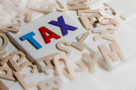 TAX concept, colourful wooden text word