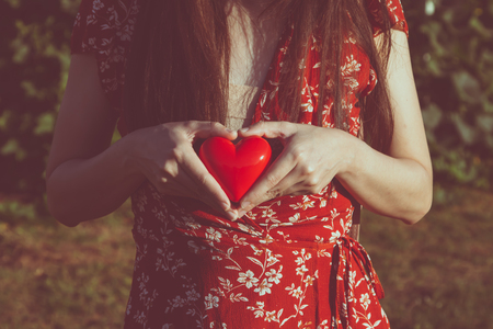 woman holding red heart, copy space in the concept of love and romantic