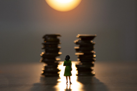 behind a miniature of woman standing with stack of coins and sunlight background, financial growth concept.
