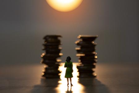 derrière une miniature de femme debout avec pile de pièces de monnaie et fond de lumière du soleil, concept de croissance financière. Banque d'images