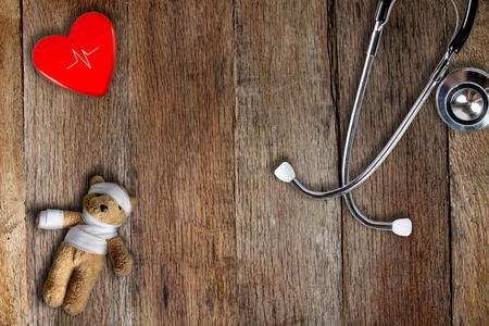 Stethoskop, Teddybär mit Verband und rotem Herzball auf Holztischform Draufsicht.