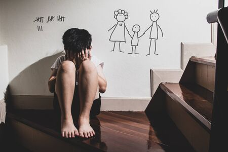 Lonely boy crying with background of family painting on the wall ,Family violence and aggression concept.