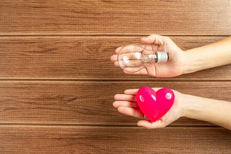 Hand holding a light bulb and pink heart with wooden background. Green energy concept ,Using environmentally friendly appliances concept.