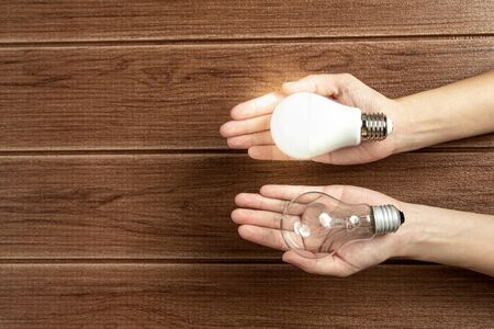 Hand holding a turned on LED light bulb on wooden background. Green energy concept, Using environmentally friendly appliances concept.