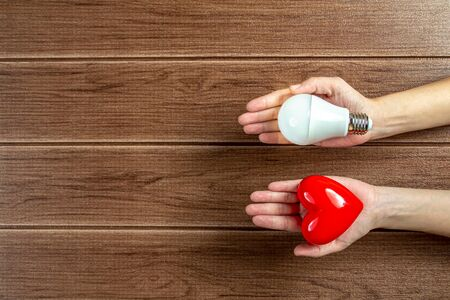 Hand holding a turned on LED light bulb and red heart with wooden table background. Green energy concept,Using environmentally friendly appliances concept.