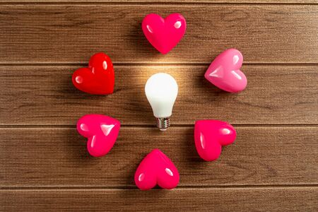 A turned on LED light bulb with pink and red heart on wooden background.Green energy concept, Using environmentally friendly appliances concept.